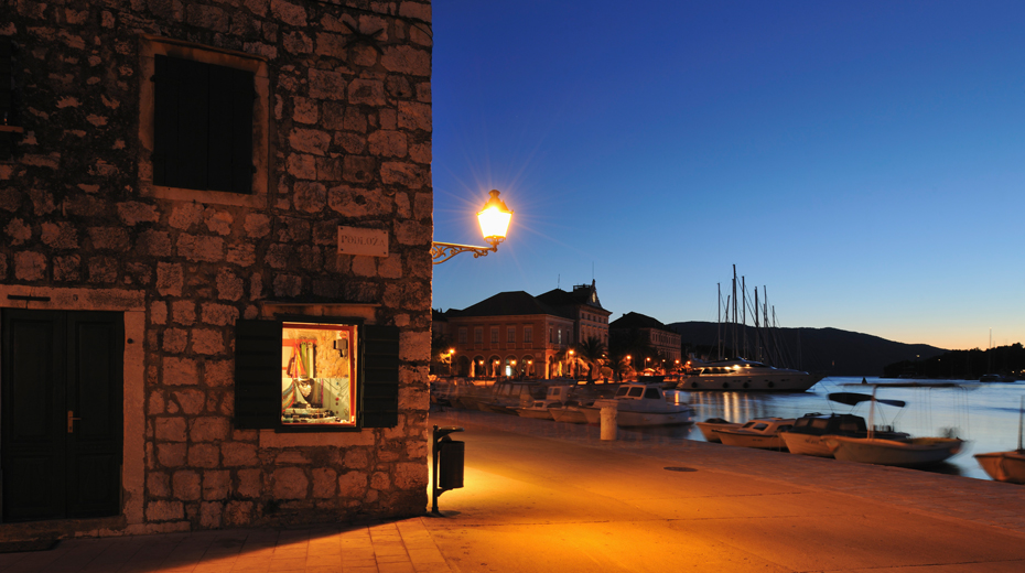 Lamp on a building beside the harbor at night,  Stari Grad,  Croatia